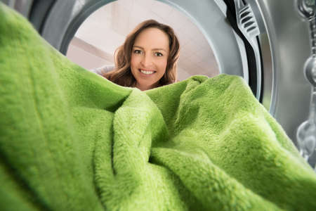 Happy Woman Putting Green Towel View From Inside The Washing Machine Appliance
