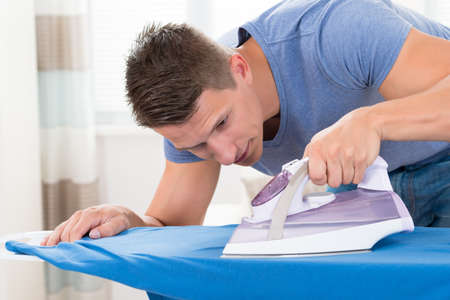 house cleaning: Young Man Ironing Clothes With Electric Iron