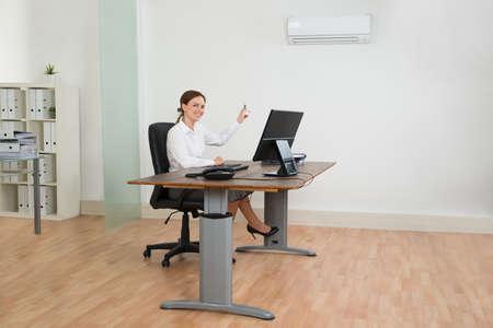 aire acondicionado: Empresaria joven que se sienta en silla Uso del acondicionador de aire en oficina