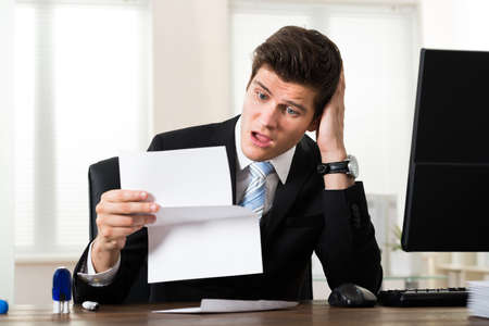 hand paper: Portrait Of Young Shocked Businessman Looking At Document In Office Stock Photo