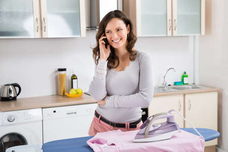 the iron lady: Young Woman Talking On Mobile Phone While Ironing Cloth On Ironing Board