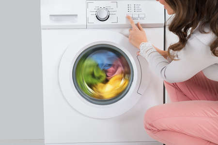 Close-up Of Young Woman Pressing Button Of Washing Machine In Kitchen Banque d'images