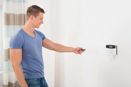 home security: Young Happy Man Operating Security Door System