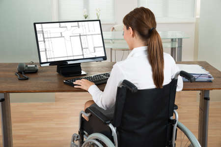 Young Female Architect On Wheelchair Looking At Blueprint On Computer In Office
