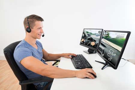 jugando videojuegos: Hombre Feliz Con Auriculares juega al juego en equipo de escritorio en casa Foto de archivo