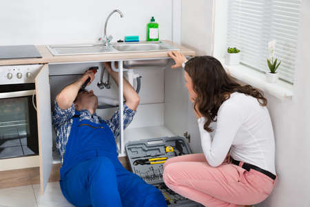 Young Repairman Repairing Sink Pipe While Woman Sitting In The Kitchen Reklamní fotografie - 44713176