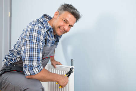warmth: Portrait Of Happy Male Plumber Fixing Radiator With Wrench Stock Photo