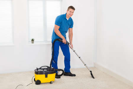 empleadas domesticas: Feliz masculino Conserje Limpieza de alfombras con aspiradora Foto de archivo