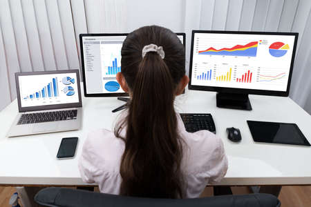 Rear View Of Businesswoman Analyzing Graphs On Multiple Computers At Desk