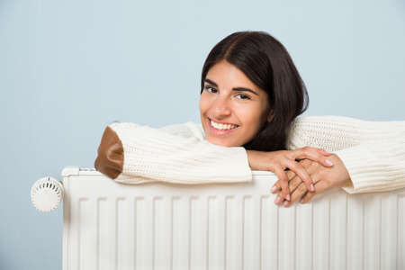 Young Happy Woman Leaning On White Radiator Stockfoto