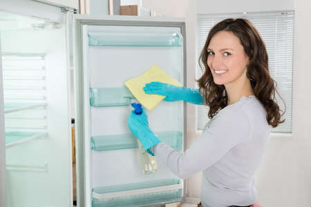 Young Woman Cleaning Refrigerator With Rag At Home Stock Photo