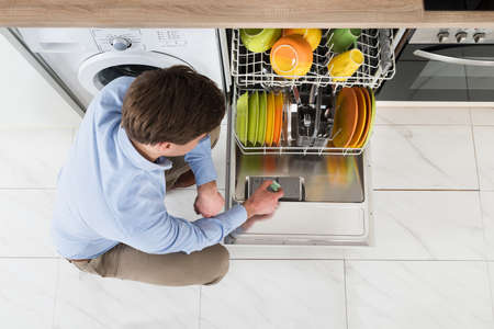 angle: Young Man Putting Dishwasher Soap Tablet In Dishwasher Detergent Box