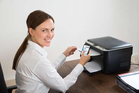 imprenta: Feliz Joven Empresaria que usa el teléfono móvil para la impresión Papel para gráficos