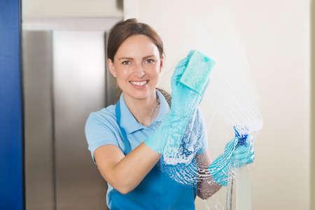 uniformes de oficina: Feliz Joven Mujer conserje de limpieza de cristal con detergente botella de spray y esponja