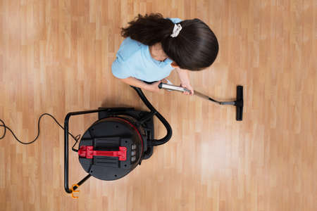 High Angle View Of Young Woman Cleaning Floor With Vacuum Cleaner
