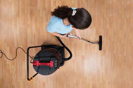 servicio domestico: Opinión de alto ángulo la mujer joven Planta de limpieza con aspiradora Foto de archivo