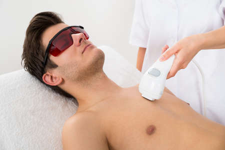 hair treatment: Close-up Of Female Worker Giving Man Laser Epilation On Chest In Salon Stock Photo