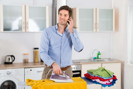 limpieza del hogar: Happy Man Talking On Mobile Phone While Ironing Clothes In Kitchen