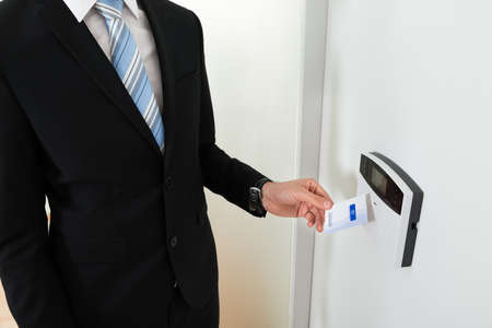 keycard: Close-up Of Businessperson Hands Holding Keycard To Open Door