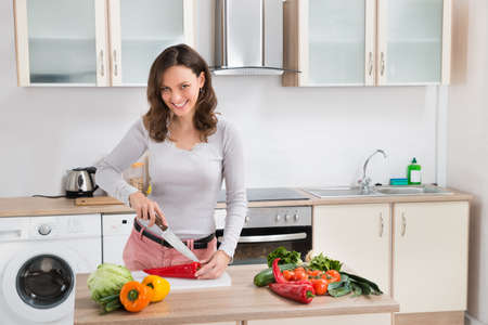 holding a knife: Young Happy Woman Cutting Vegetables In Kitchen
