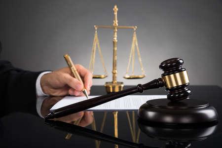 Nahaufnahme Der Richter Schreiben auf Papier mit Hammer und Skala Am Schreibtisch Standard-Bild