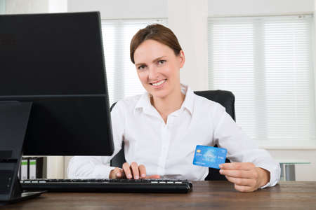 accounts: Young Businesswoman With Credit Card And Using Computer At Desk Stock Photo