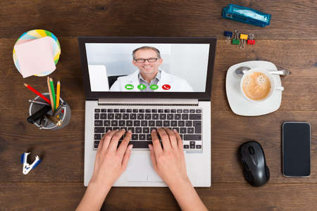 web conference: Close-up Of Person Videochatting Online With Doctor On Laptop Stock Photo