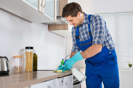 countertop: Young Worker In Overall Cleaning Countertop With Rag In Kitchen
