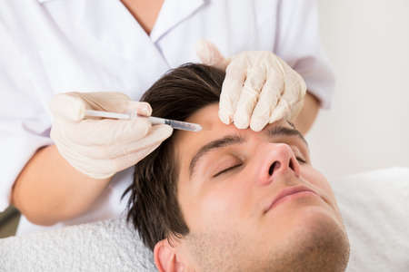 Young Man Having Botox Treatment At Beauty Clinic Stockfoto