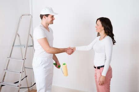 pintor: Mujer Hermosa Joven Estrechar las manos Para pintor con el rodillo de pintura en el hogar Foto de archivo