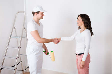 hand holding house: Young Beautiful Woman Shaking Hands To Painter With Paint Roller At Home