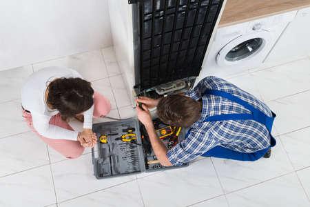 refrigerator: Young Repairman Repairing Refrigerator In Front Of Beautiful Woman Stock Photo