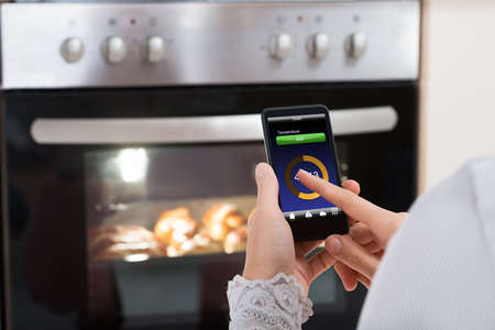 woman on phone: Close-up Of Person Hands Operating Oven Appliance With Mobile Phone