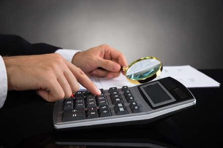investigacion: Primer Del Empresario Inspección de facturas con lupa y calculadora Foto de archivo