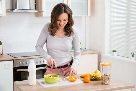 a jar stand: Beautiful Young Woman Preparing Breakfast In Kitchen Stock Photo
