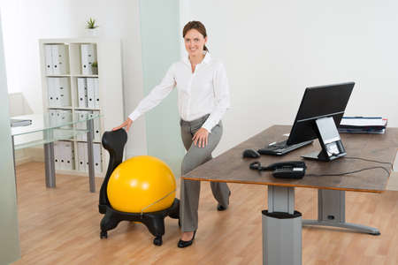 woman work: Young Happy Businesswoman Exercising With Pilates Ball On Chair In Office