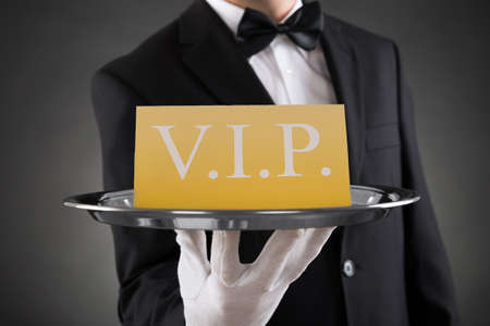 Close-up Of Waiter Showing Vip Text On Banner Stockfoto