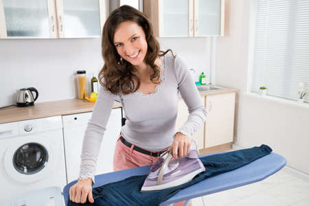Happy Woman Ironing Trousers With Electric Iron At Home