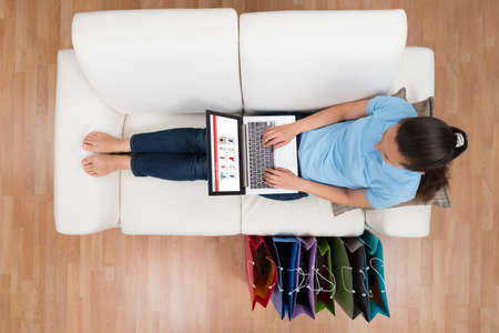 Woman On Sofa With Shopping Bags Browsing Shopping Site On Laptop