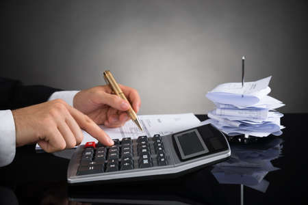 calculating: Close-up Of Businessperson Calculating Invoice With Calculator At Desk
