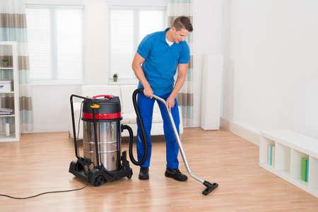 personal de limpieza: Feliz masculino Janitor Aspirar piso de madera en casa Foto de archivo