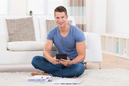 gospodarstwo domowe: Młody mężczyzna siedzi na dywan Obliczanie budżetu z kalkulatorem Zdjęcie Seryjne