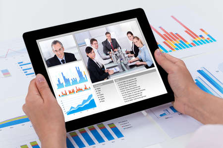 conferencing: Close-up Of Person Video Conferencing With Colleagues On Digital Tablet Stock Photo