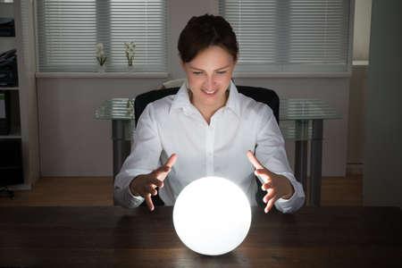 vision futuro: Empresaria joven que mira en el futuro en una bola de cristal en la oficina Foto de archivo
