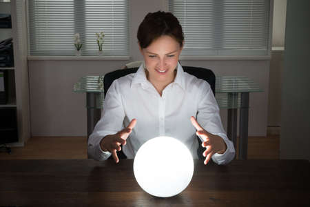 ball: Young Businesswoman Looking Into The Future In A Crystal Ball In Office Stock Photo