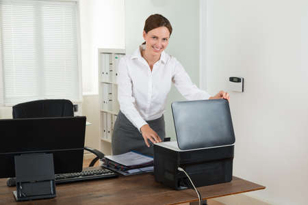office printer: Young Happy Businesswoman Using Printer In Office