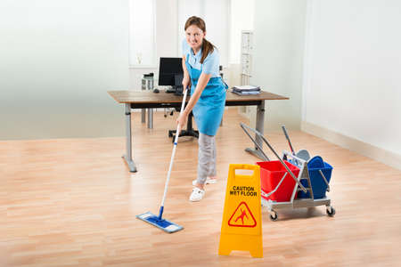 Happy Female Janitor With Cleaning Equipments Cleaning Hardwood Floor In Office Zdjęcie Seryjne