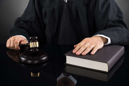 tribunal: Close-up Of Male Judge With Gavel And Book At Desk Stock Photo