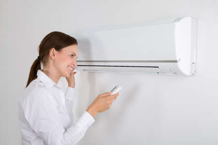 fresh girl: Happy Businesswoman Operating Air Conditioner Mounted On White Wall In Office Stock Photo