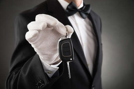 hand key: Close-up Of Waiter Holding Car Key In Hands Stock Photo